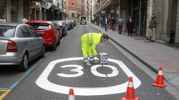 Un operario pinta una señal de 30 km/h./